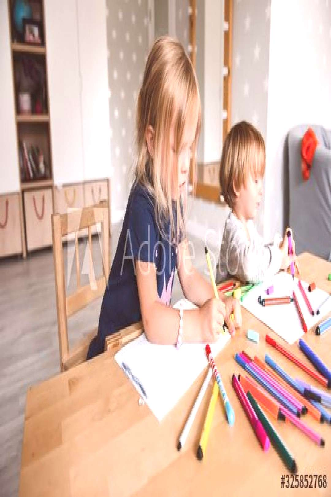 Little boy with sister drawing with felt-tip pens ,